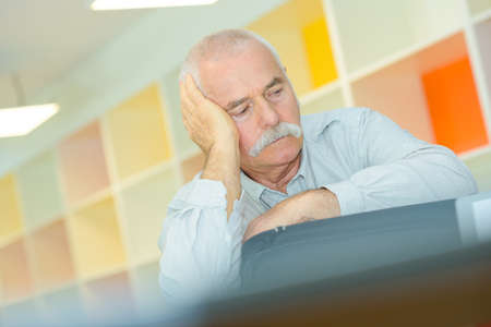 elderly man with hand on his temple has a headache Stock Photo