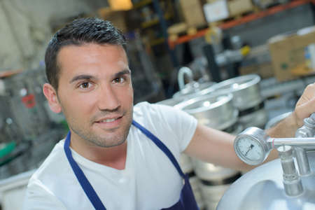 the brewer: cheerful man in white uniform using bottling equipment on brewery