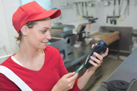 worker entering pin code to bank terminal with credit car Stock Photo