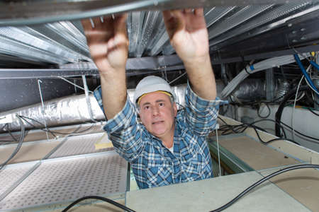 man - electrician does an electrowiring