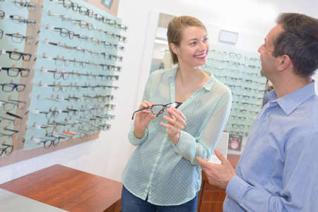 ophthalmologist and female choosing glasses at a optics store Stock Photo