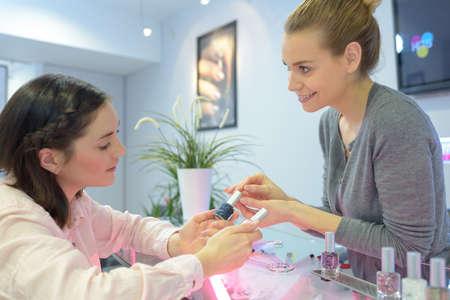 woman choosing new nail polish color at store