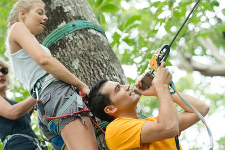 clambering: boyfriend preparing rope for girlfriend in an adventure park Stock Photo