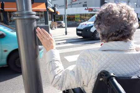 invalidity: Disabled woman waiting in wheelchair at zebra crossing