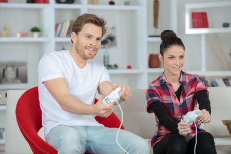 jugando videojuegos: happy couple playing video games on console and having fun