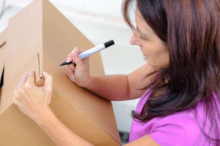 cardbox: woman writing on cardboard box