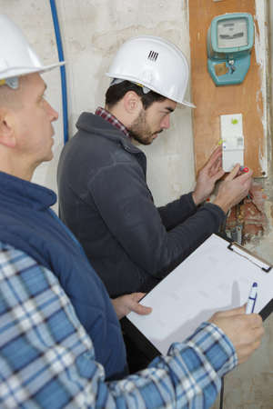 mounting: young electrician builder engineer screwing equipment in fuse box
