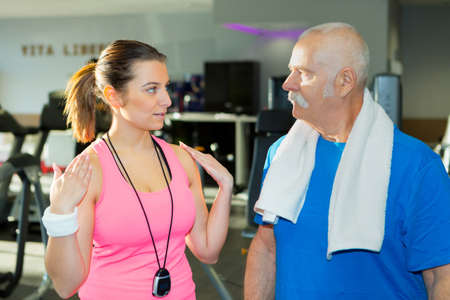 centered: elderly man and personal fitness trainer