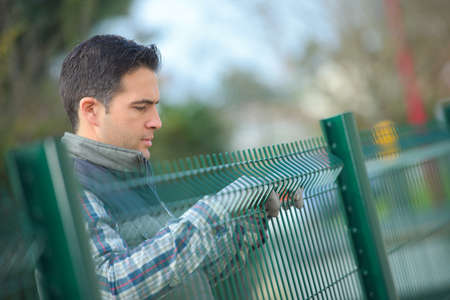 worker putting up a garden fence Stock Photo