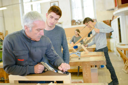 apprentice with adult in carpentry school working on wood Stock Photo