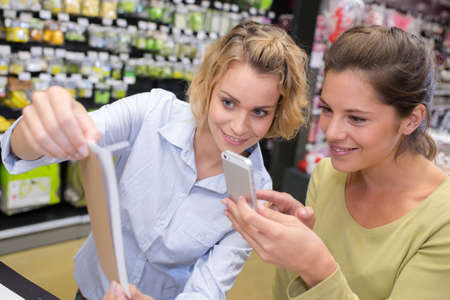 considering: women taking a picture with mobile phone in a shop Stock Photo
