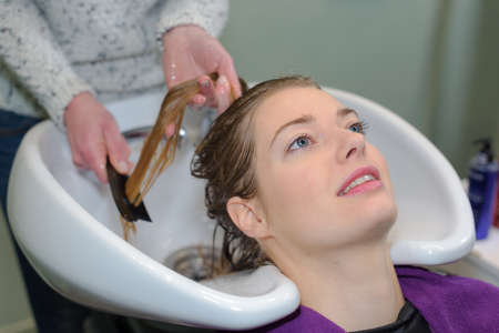 client is resting while her hair is being cleansed Stock Photo