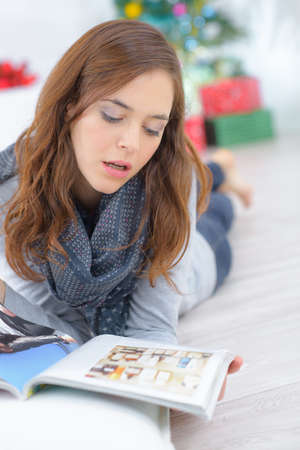 was: pretty woman reading magazine on the floor Stock Photo