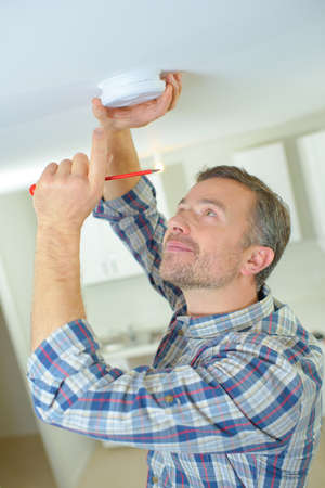 was: fitting a fire alarm to be safe Stock Photo