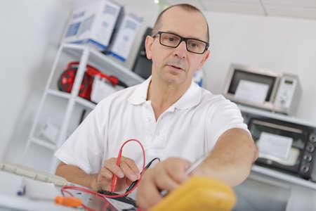 Man using an electronic measuring instrument