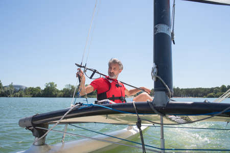 cruising: man sailing with sails out on a sunny day