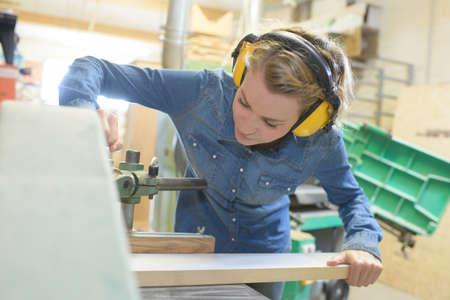 Woman using band-saw