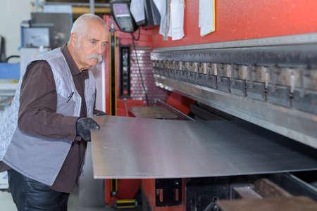 man controlling hydraulic press machine for cutting steel