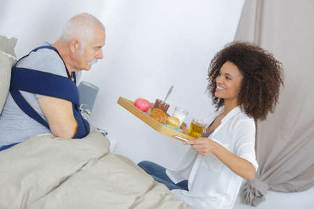 beautiful young girl is giving food to handsome old man