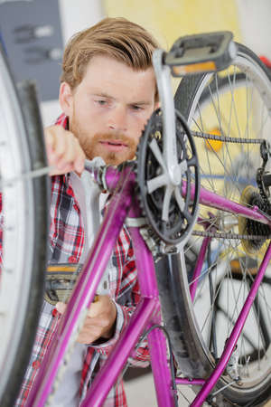 to mend: Man trying to fix bike chain