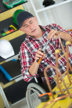 Wheelchair user fixing cooper pipes