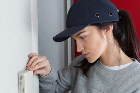 female technician set the thermostat at house Stock Photo