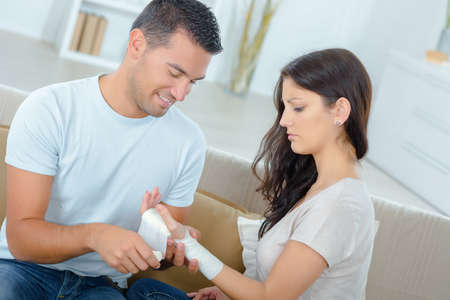 man assisting woman with a wrist bandage