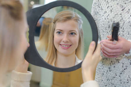 satisfied girl customer looking at herself on the mirror