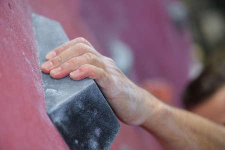 climber hands holding artificial boulder in climbing gym closeup shot