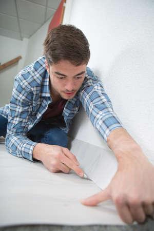 Jong mannelijk snijden tapijt met mes Stockfoto