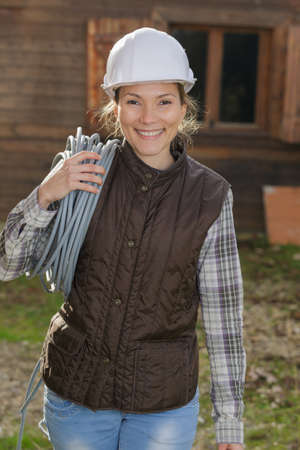 happy female construction worker carrying wires Stock Photo