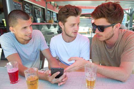 designated: Three men in bar looking at cellphone