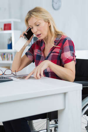 woman on a wheelchair at a home on the phone