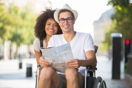handicapped man in wheelchair and girlfriend on holidays Stockfoto