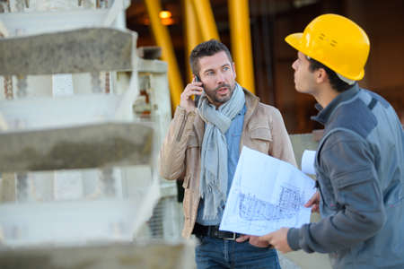 techincal: two male industrial engineers looking at techincal drawing plans