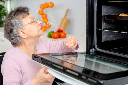 grandmother on wheelchair putting pie in oven Stock Photo