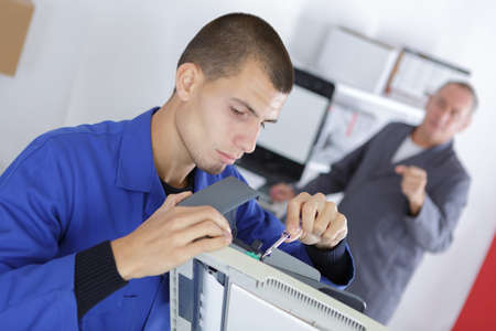 printout: closeup shot young male technician repairing digital photocopier machine