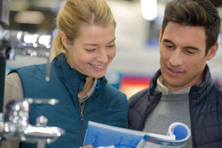 young woman in overalls assisting a customer Stock Photo