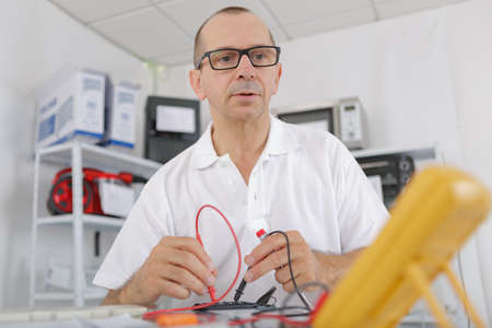 senior man calibrating with a digital multimeter