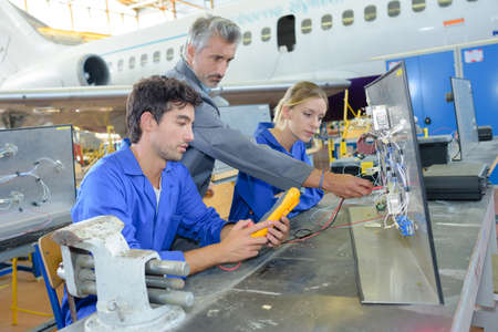 19 year old boy: teacher helping students training to be car mechanics Stock Photo