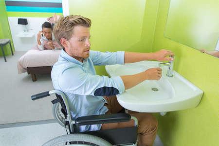 incapacity: man on wheelchair washing hands in bathroom
