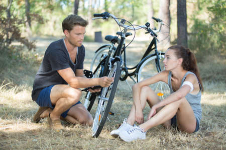 couple fixing a bike outdoors Stock Photo