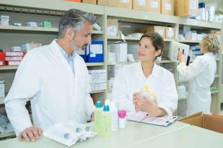 dispensary: pharmacists discussing in pharmacy Stock Photo