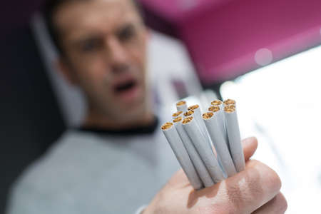 man holding cigarettes Stock Photo