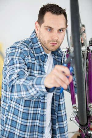 man fixing bike wheel in store Stock Photo