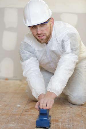 Man begint de oude vloertegels te verwijderen Stockfoto