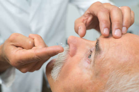 doctor putting contact lenses to patient Banco de Imagens