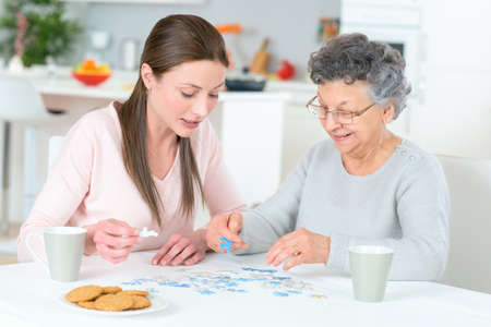 the grand daughter: grand daughter and grand mother working on puzzle Stock Photo
