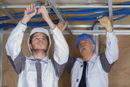 young male electrician with mentor wiring in ceiling