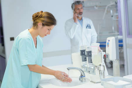 젊은 아름 다운 간호사 손을 씻어.